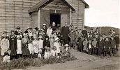 Vice Provincial Patrick Mulhall and Fr. Augustine Duke with congregation outside of the church. East Kildonan, Winnipeg, MB, 1914.